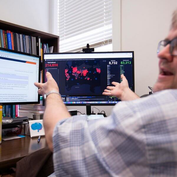 Sean Walker gestures at computer screen with Coronavirus map displayed