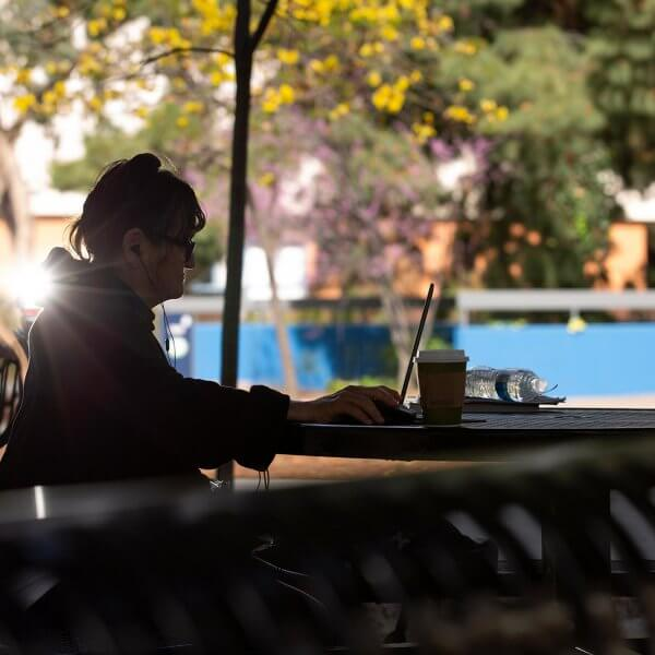 Heather Paredez sits at a table on campus with her laptop
