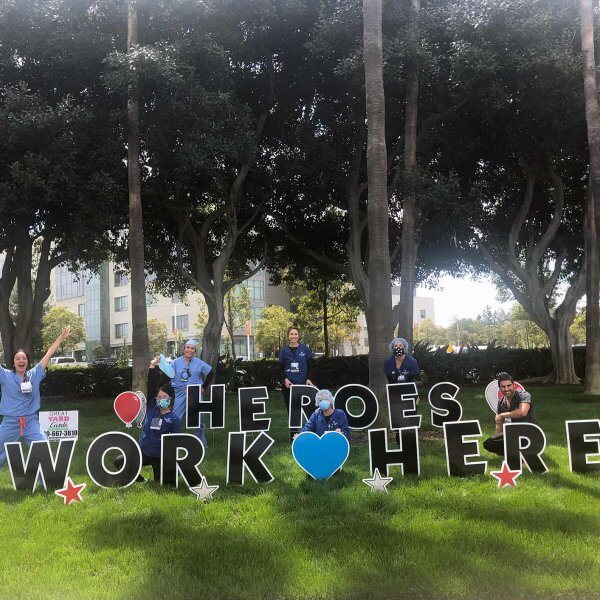 """Group of health care workers in front of a sign that reads """"Heros Work Here"""""""