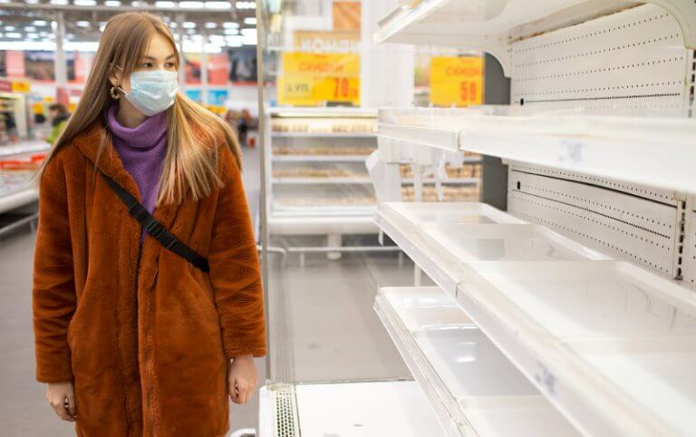 woman in a grocery store wearing a mask looking at empty shelv es