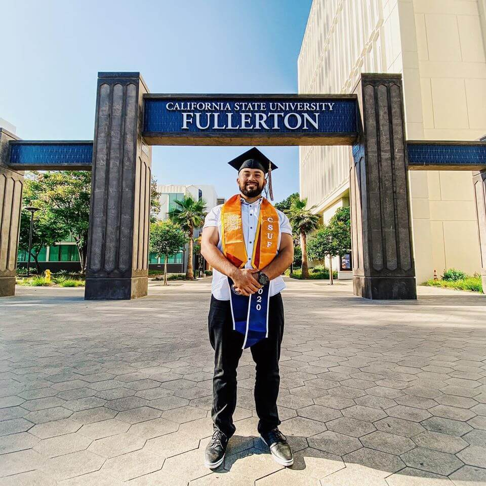 man standing in front of sign with Cal State Fullerton spelled out