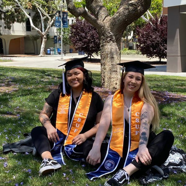 two women in grad regalia sitting on grass and smiling