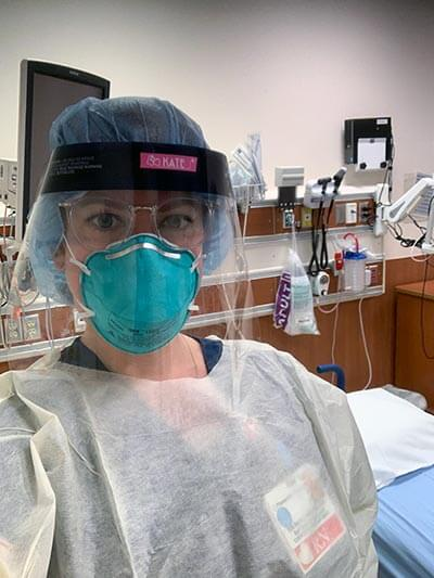 a woman wearing surgery scrubs, mask and a plastic visor