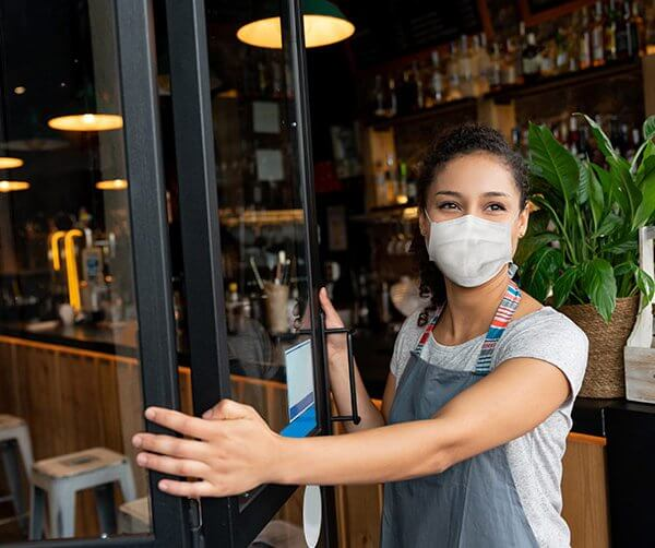 a woman wearing a mask opening the door of a restaurant