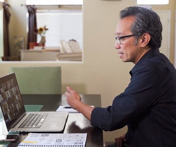 a man wearing eyeglasses sitting and looking at a laptop teaching an online class