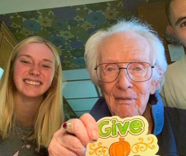 elderly man wearing glasses smiling and with a young woman and man/