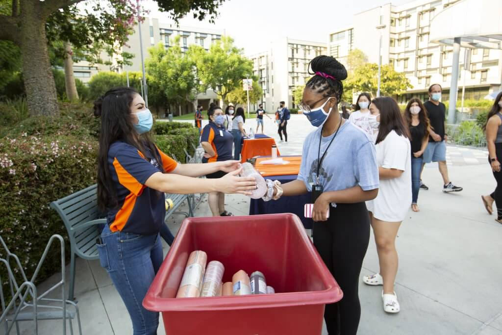 several people helping during move-in day in a courtyard wearing face masks
