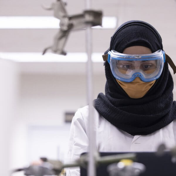 A young woman wearing a white lab coat, safety goggles and a face mask in a science lab