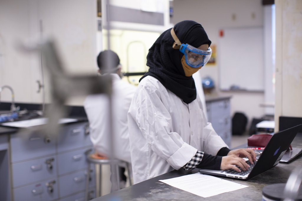 a woman wearing safety googles, whote lab coat, face masks in a science lab