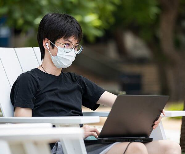 a man wearing eyeglasses working on a laptop